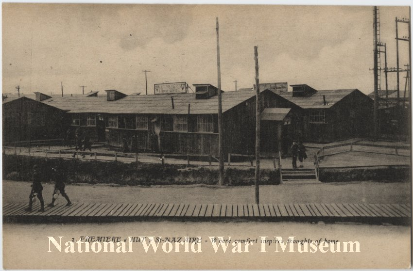 Soldiers walk across a boardwalk and around the paths around a series of barracks-like buildings that all look the same.